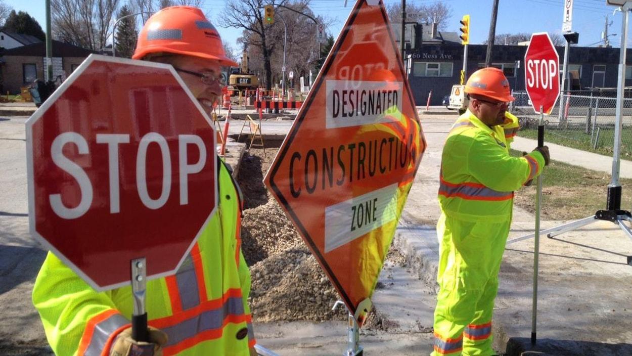 Des travailleurs de la construction tiennent des panneaux de signalisation sur un chantier.