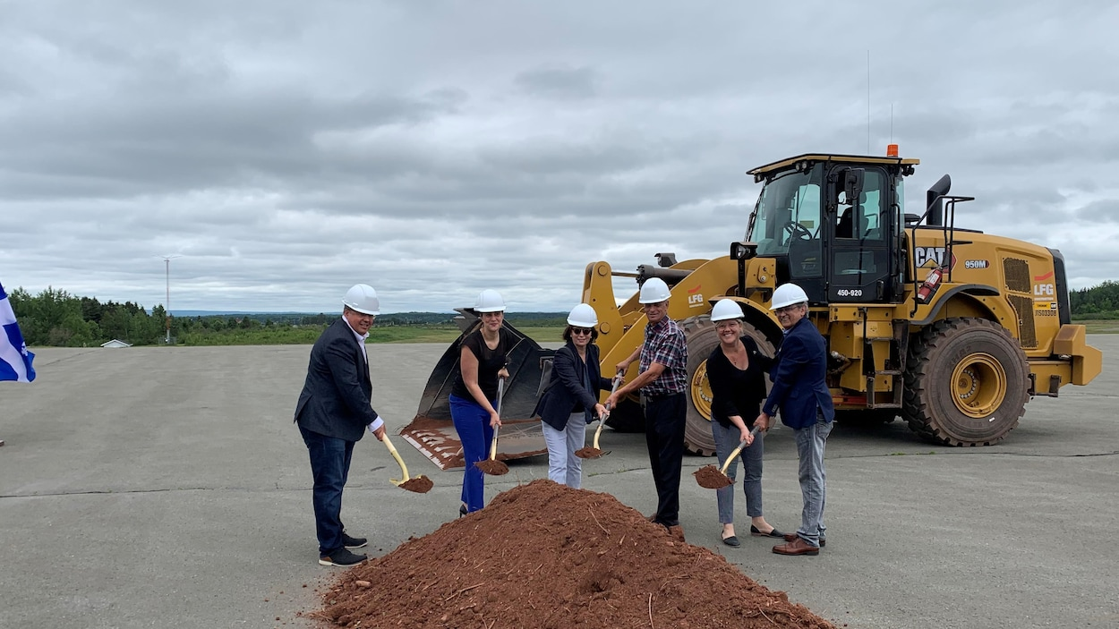 Six personnes soulèvent une pelletée de terre sur la piste de l'aéroport de Grande-Rivière.