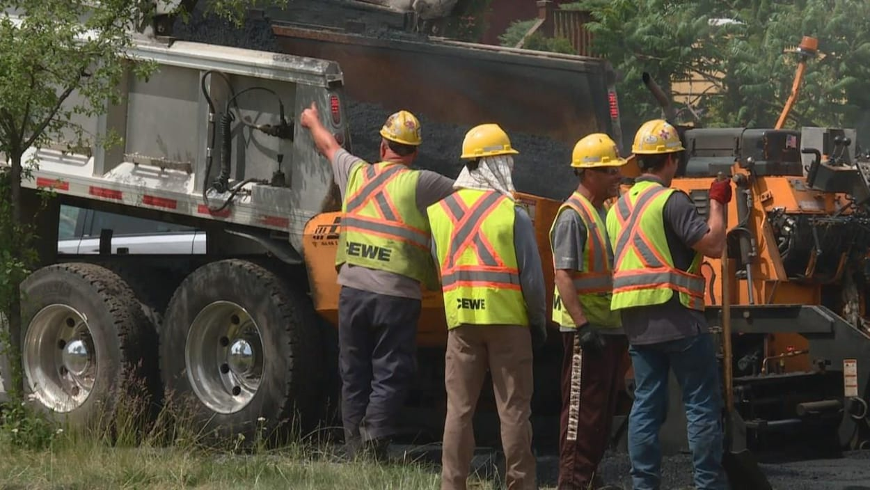 Des ouvriers de Fortis BC, devant de l'équipement lourd, à Vancouver.