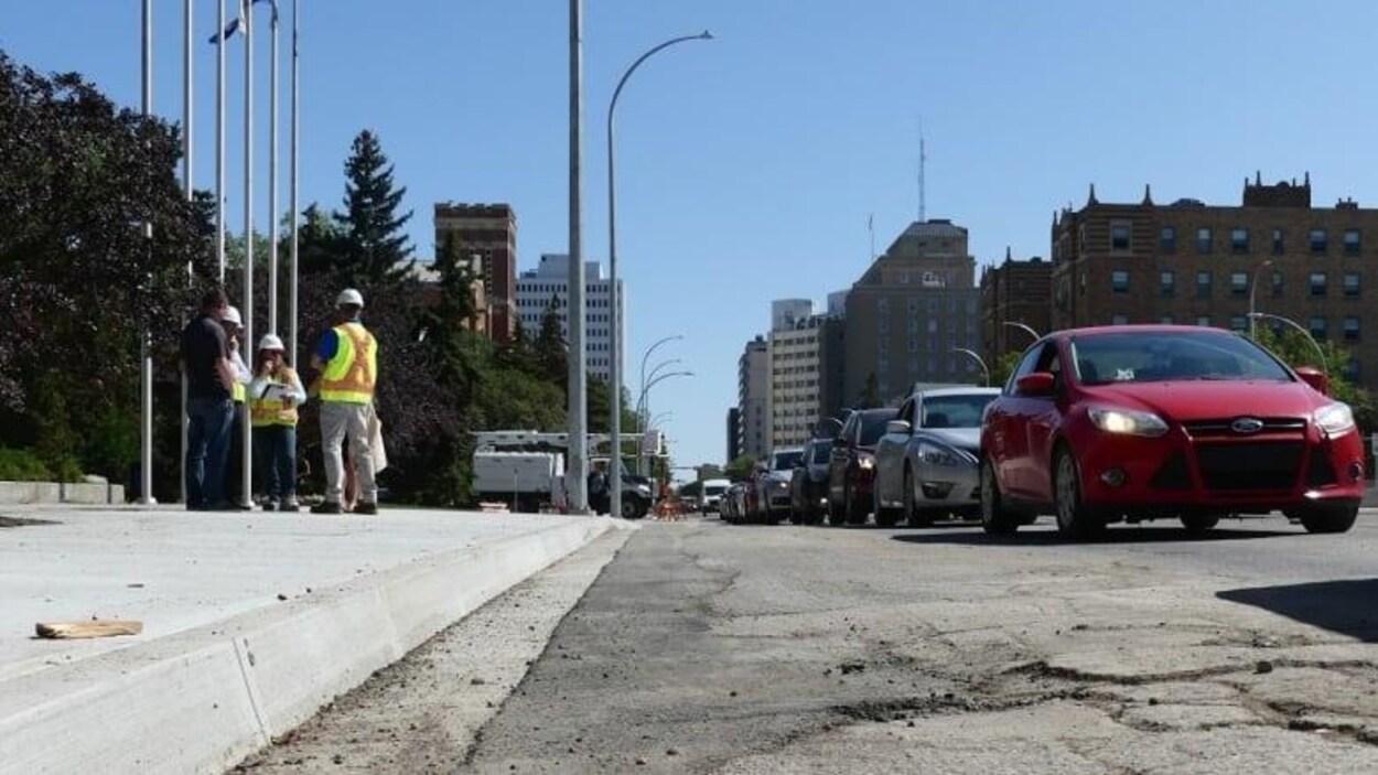 Des voitures sont prises dans un embouteillage dans une rue en réparation.