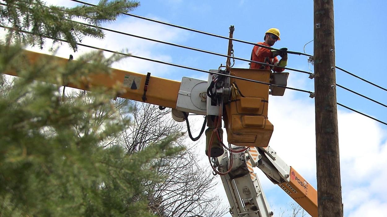 Un homme, dans une petite cabine d'une grue d'Hydro-Québec jaune, répare des fils électriques.