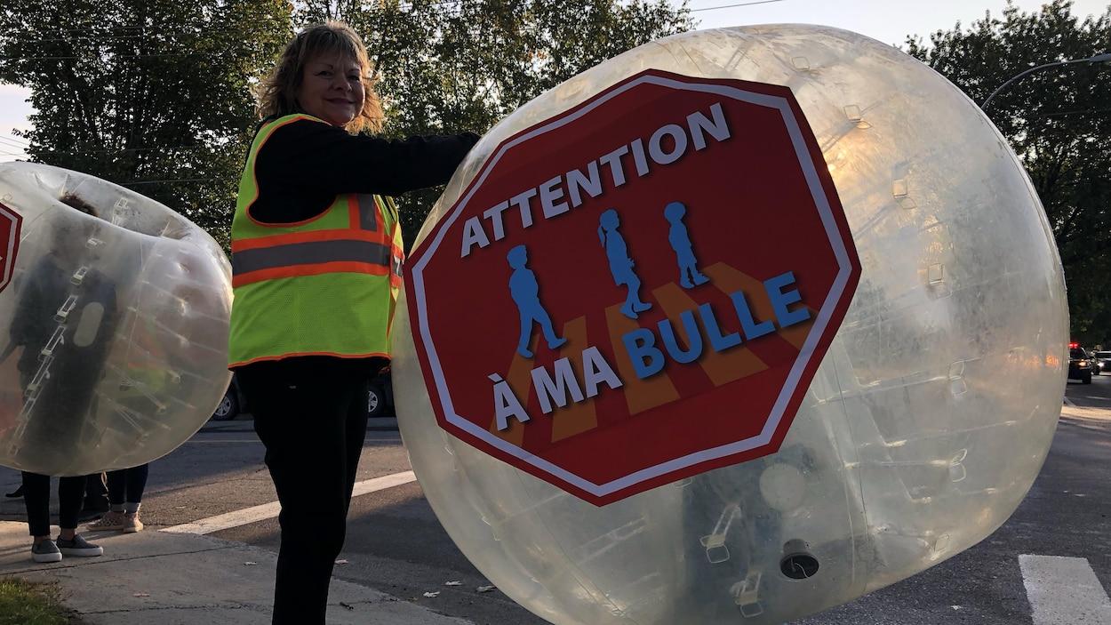 Une femme installe une bulle gonflable sur un enfant en bordure de la route à Alma.