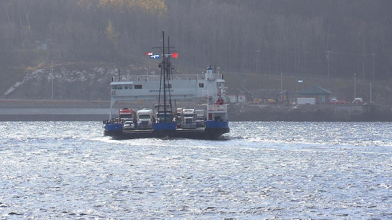 Un traversier flotte sur l'eau et semble rempli de véhicules lourds.