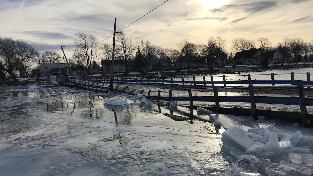 On voit un ponton sur l'eau dont les barrières sont toutes déformées pas de gros morceaux de glace.