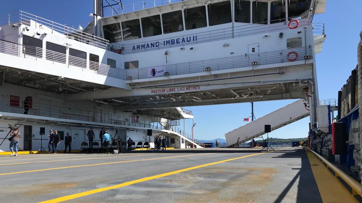 Photo du NM Armand Imbeau II prise sur le pont servant à accueillir les voitures. On aperçoit une corde d'amarrage, la passerelle du navire et une rampe d'accès pour les piétons.