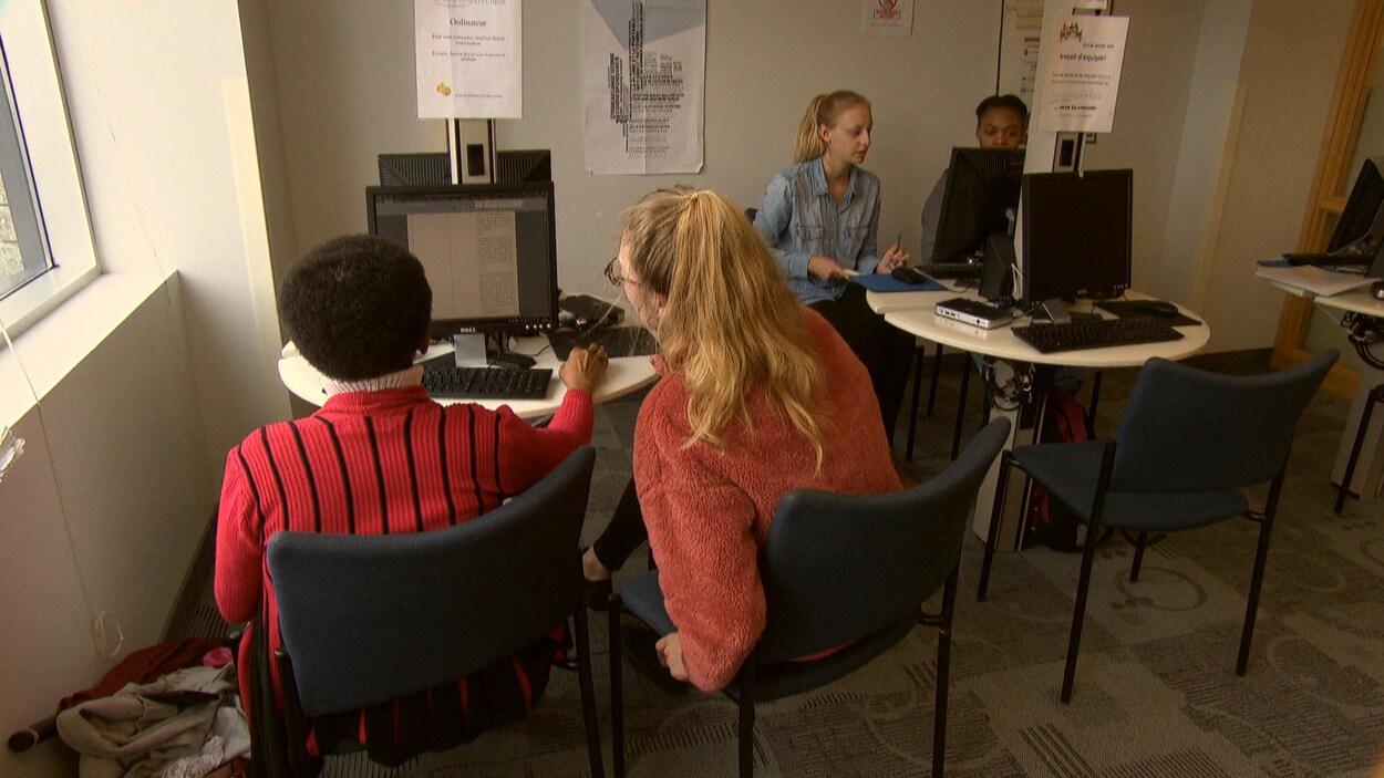 Dans le local, deux tutrices installées devant des ordinateurs aident chacune une étudiante avec leurs travaux.