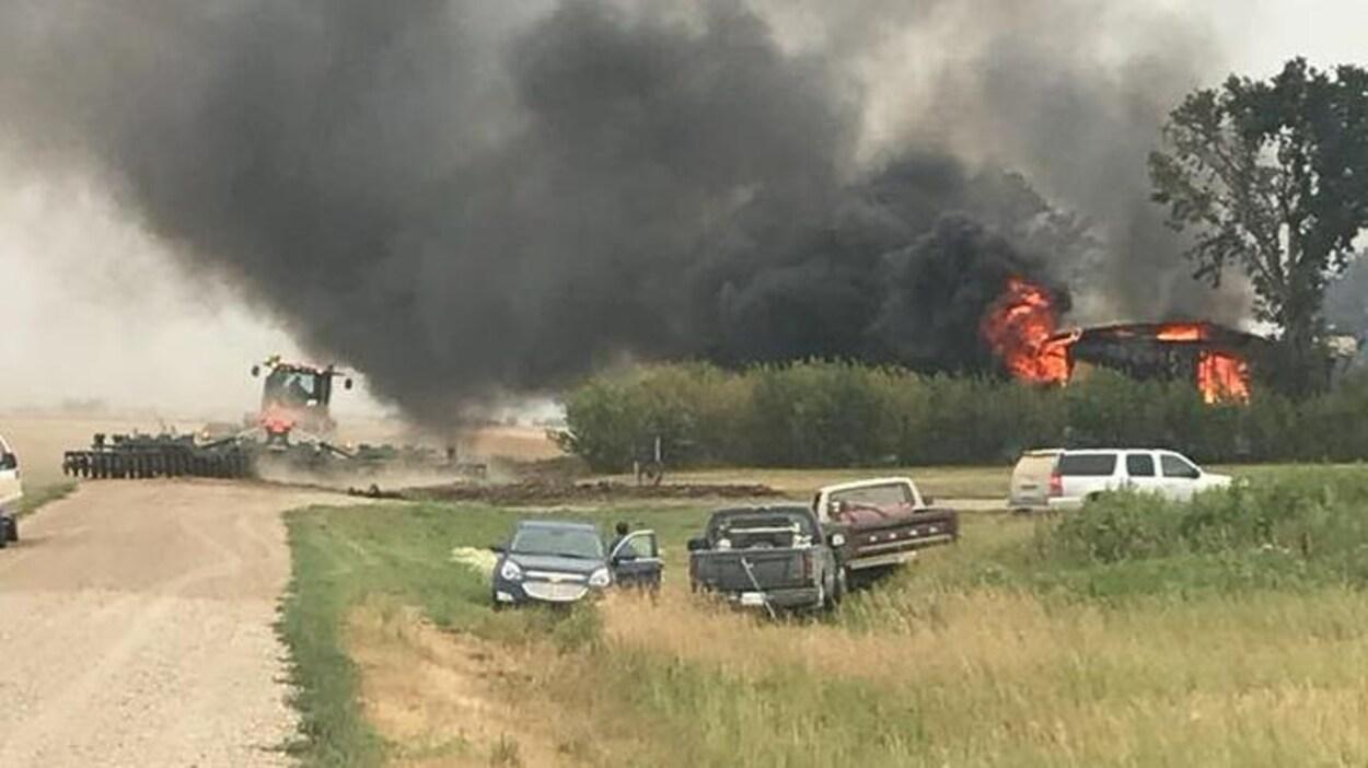 Une épaisse fumée s'élève au-dessus d'une maison en flammes. Plusieurs voitures sont stationnées derrière les arbres qui bordent la maison. À gauche, un homme dans un tracteur s'assure que les flammes ne se dispersent pas dans les champs.
