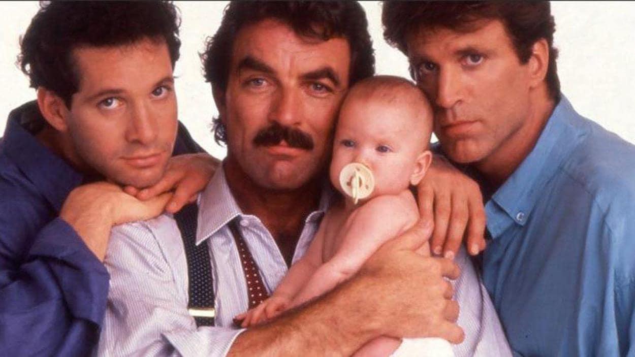 Trois hommes entourent un bébé.