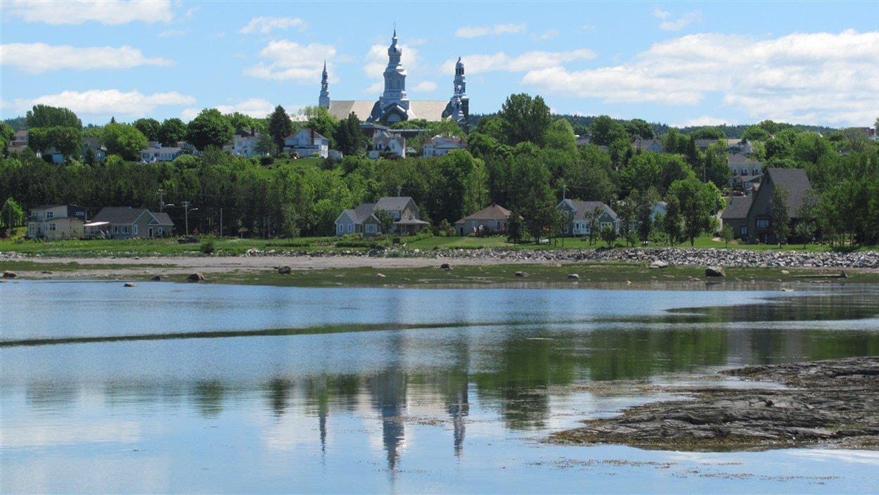 On distingue les clochers de l'église de la municipalité de Trois-Pistoles, derrière des arbres en bordure du fleuve.