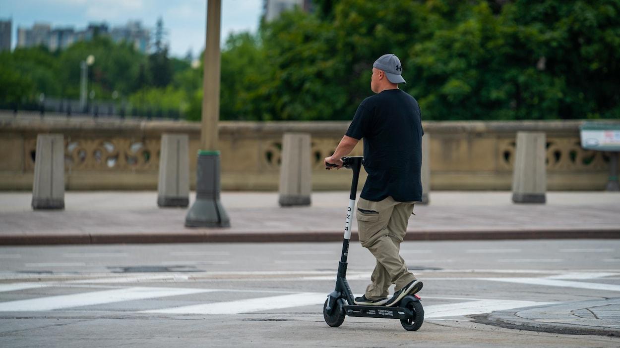 Un homme circule sur une trottinette au centre-ville.