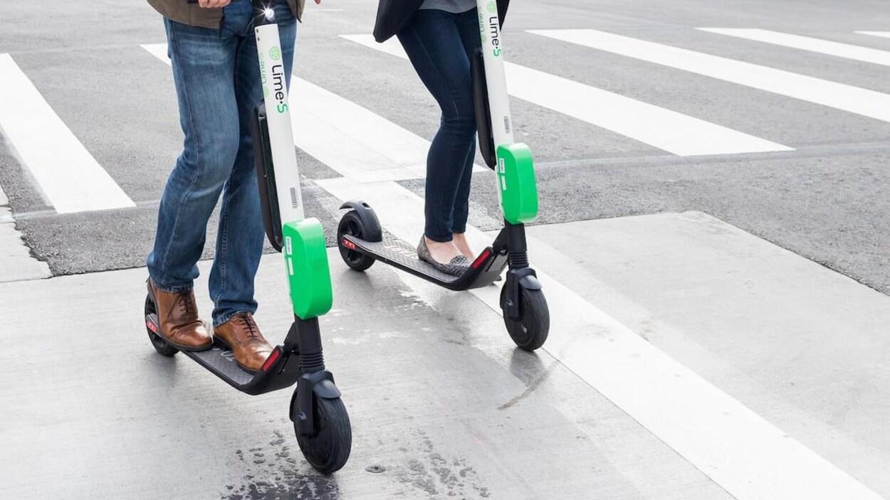 Deux personnes circulent en trottinette dans un environnement urbain.