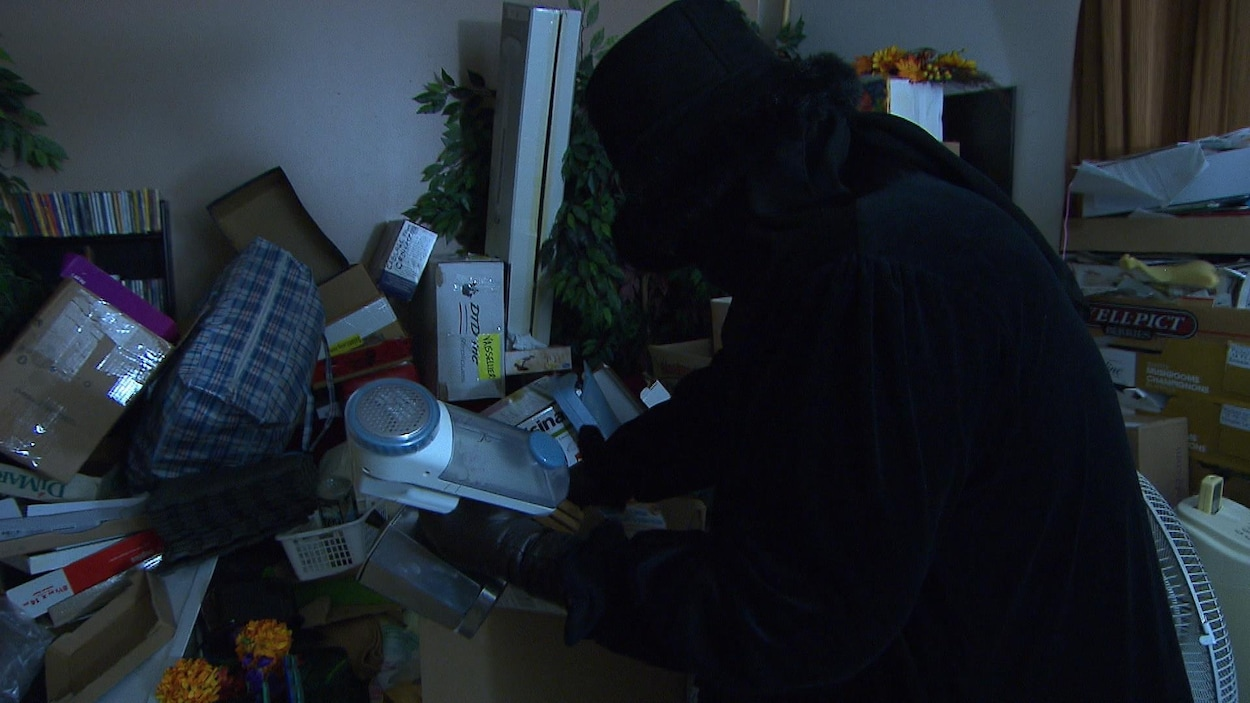 Une femme vêtue de noir tient l'un des nombreux objets qui sont éparpillés dans son appartement.