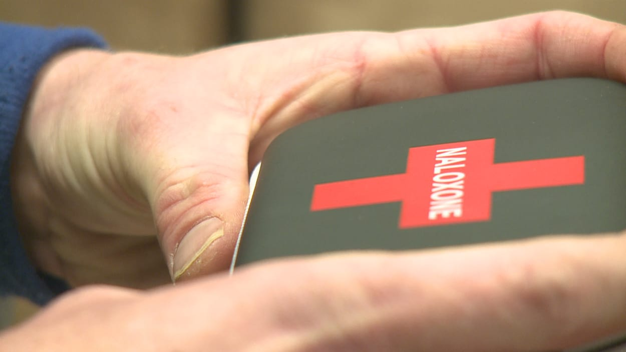Gros plan sur des mains qui tiennent une petite boîte carrée avec une croix rouge sur laquelle est inscrit naloxone.