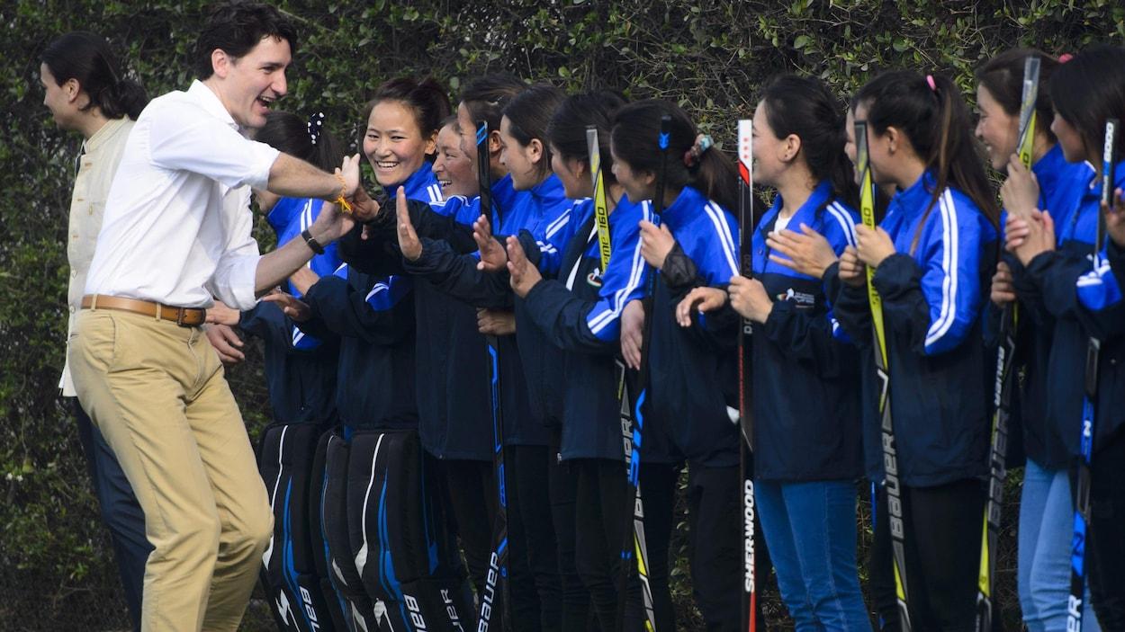 Justin Trudeau et l'équipe féminine de hockey sur glace de l'Inde lors d'une démonstration au Haut-commissariat canadien de New Delhi samedi