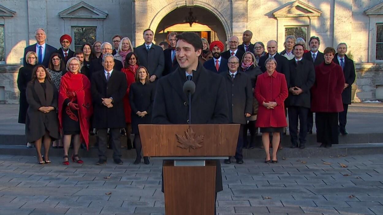 Justin Trudeau au micro, à l'extérieur du parlement, alors que ses ministres sont rassemblés derrière lui.