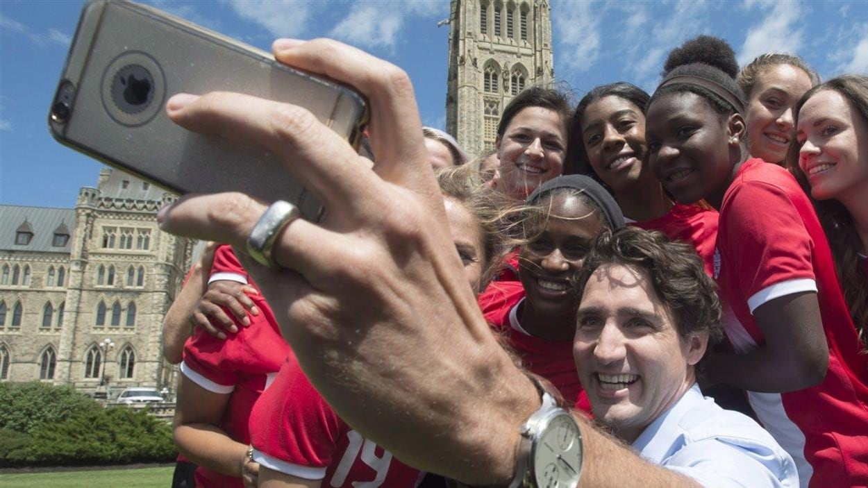 Justin Trudeau fait un égoportrait avec l'équipe nationale de soccer devant le parlement, à Ottawa.
