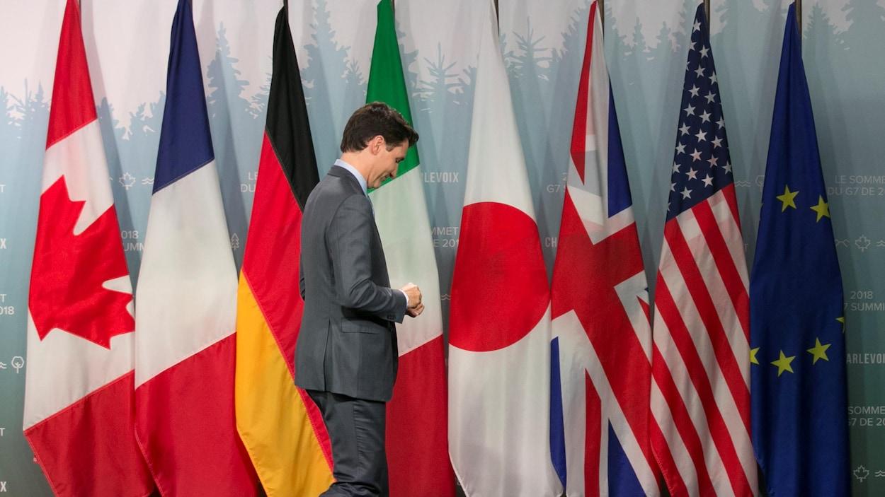 Le premier ministre canadien, Justin Trudeau, marche devant les drapeaux des membres du G7 lors de la rencontre du Sommet du G7 à La Malbaie, en juin.
