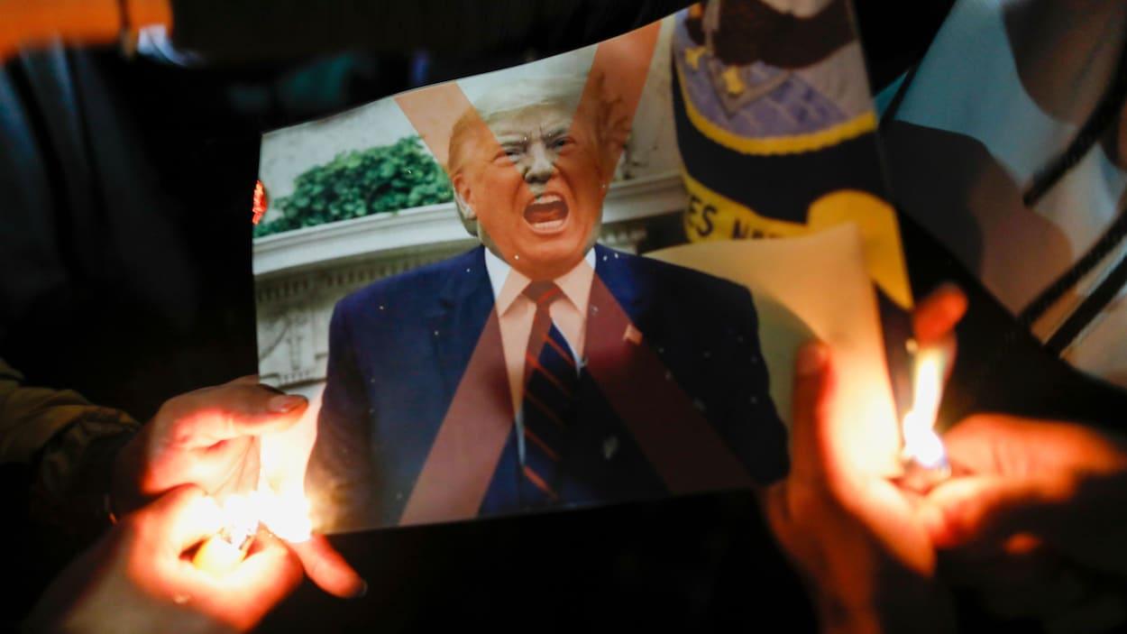 Une photo de Trump en train de crier brûlée par des manifestants avec des briquets.