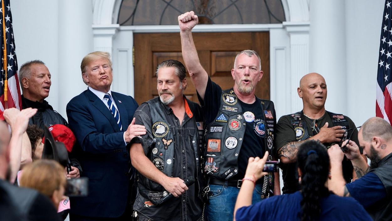 Un homme portant un veston et une cravate tient le bras d'un motard portant une veste en cuir alors qu'un autre lève un poing dans les airs et qu'un troisième a la main droite sur son cœur