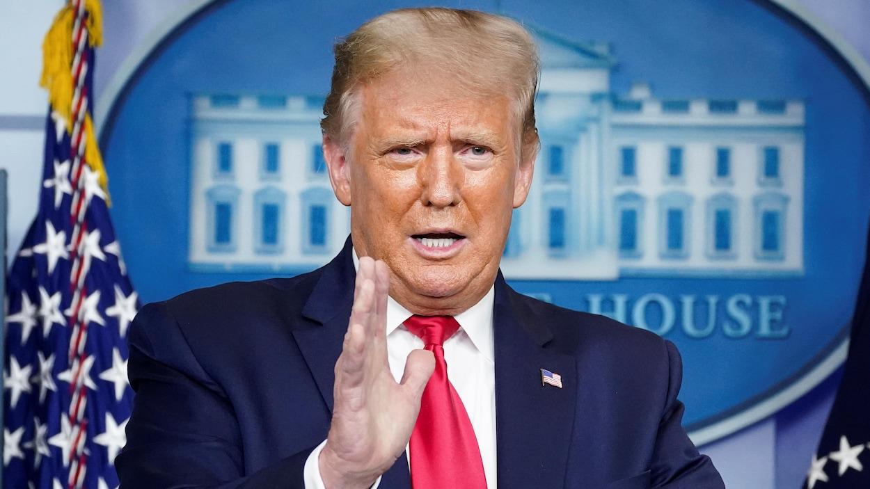 Donald Trump, la main levée, s'adresse aux reporters réunis à la Maison-Blanche