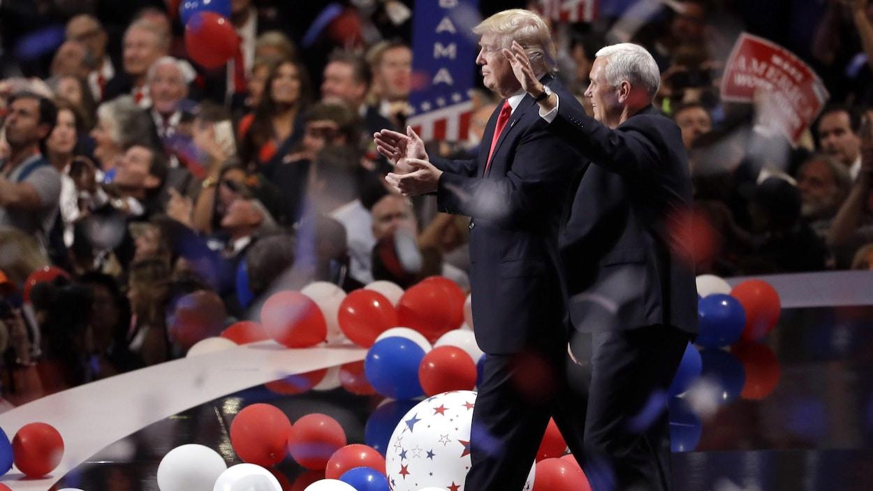 Donald Trump et Mike Pence marchant ensemble sur une scène jonchée de ballons, devant les partisans républicains, qui sont debout.