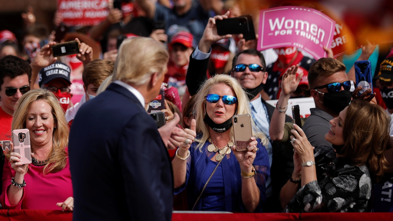 Donald Trump de dos, devant des partisans. Il fait un signe de pouce en l'air à une femme, qui fait la même chose.