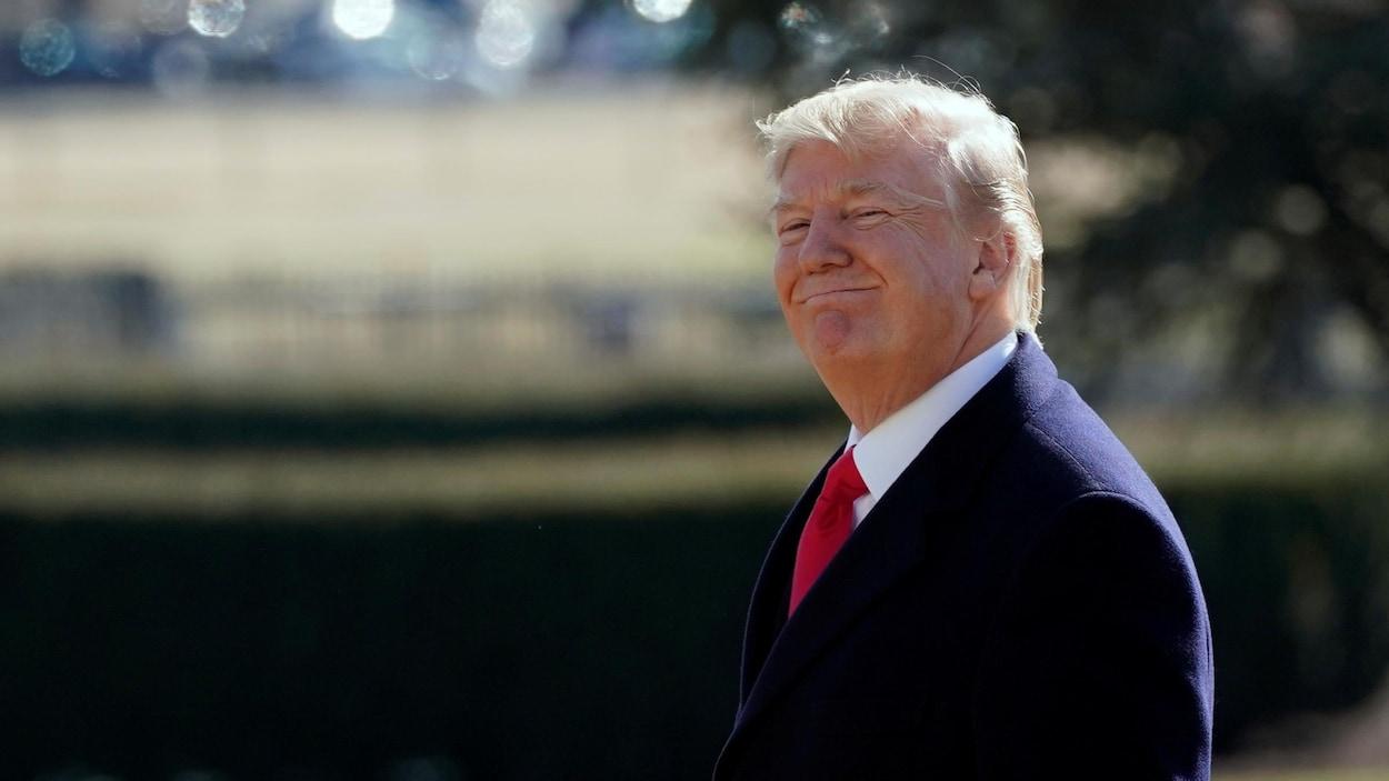 Le président américain, Donald Trump sourit à la caméra à l'extérieur de la Maison-Blanche.