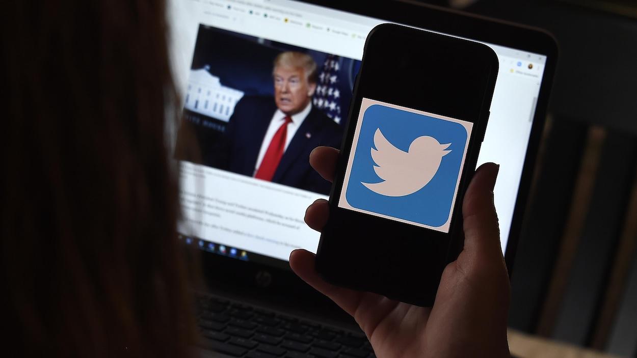 Dans cette illustration photographique, un logo Twitter est affiché sur un téléphone portable avec la page Twitter du président Trump en arrière-plan.