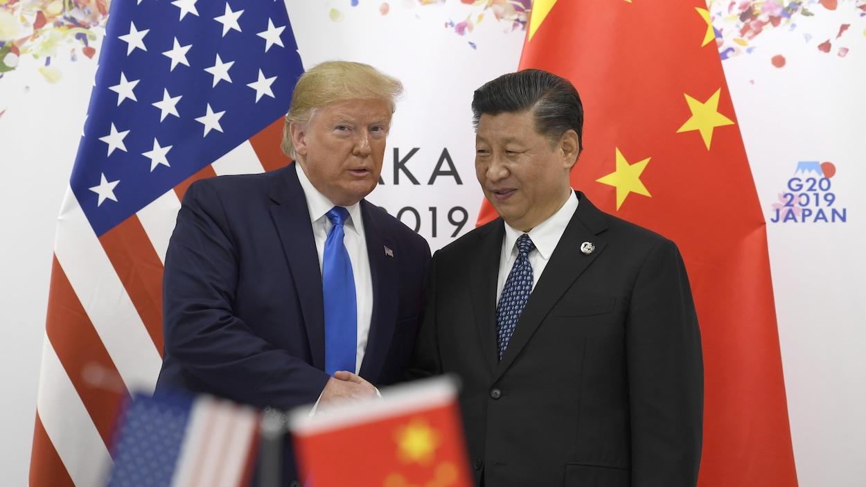 Donald Trump serre la main de Xi Jinping devant leur drapeau respectif.