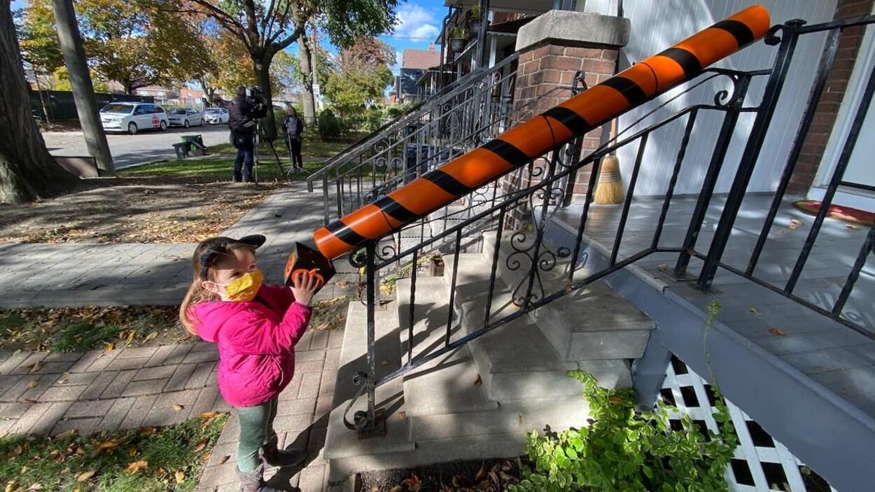 Une petite fille devant un tuyau de PVC orange