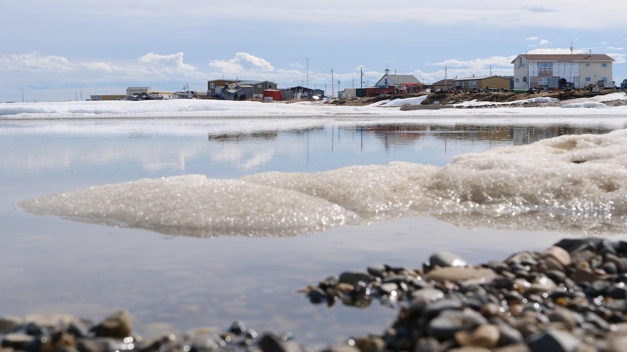Un village sur la côte derrière une étendue d'eau à moitié gelée.
