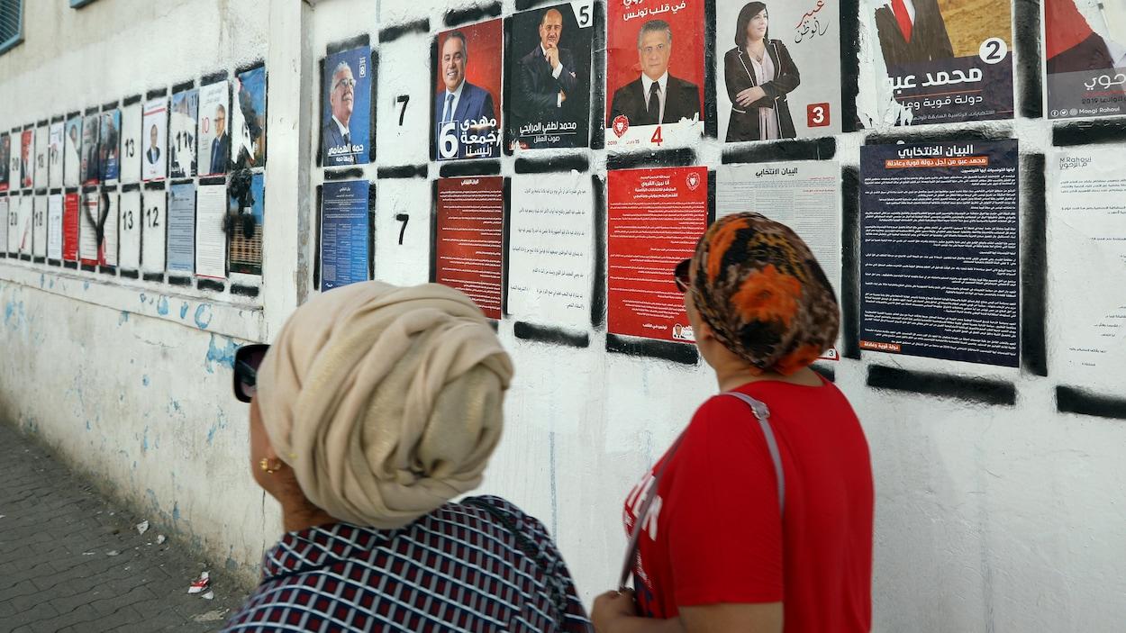 Deux femmes passent devant un mur couvert d'affiches des nombreux candidats à l'élection présidentielle.