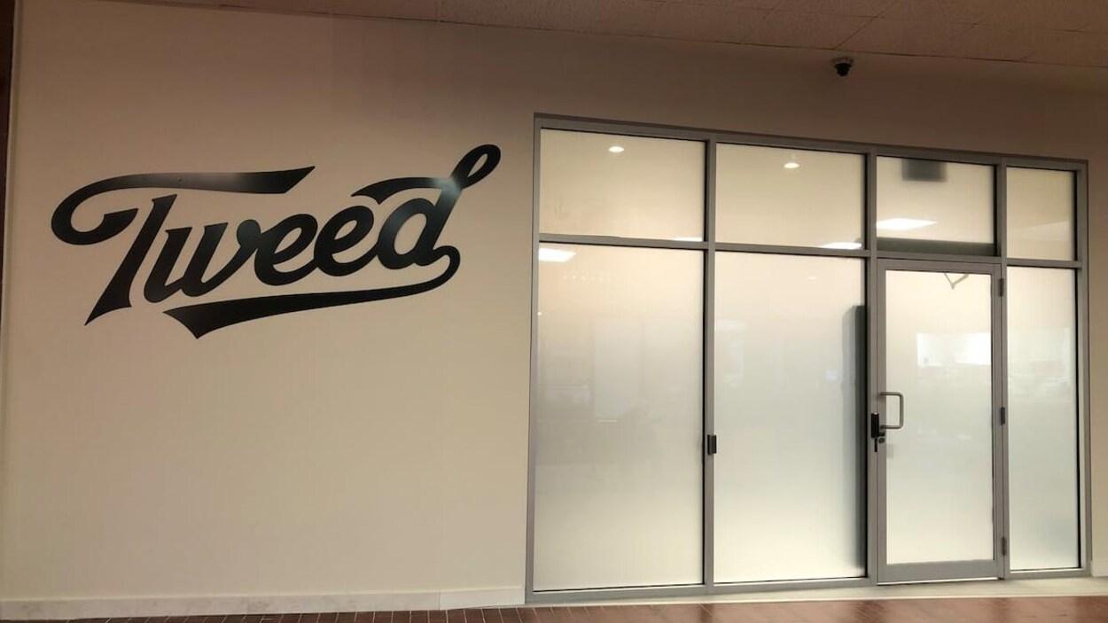 Sur un mur blanc, il est écrit Tweed en grand et en noir à côté d'une porte et de fenêtres en verre givré.