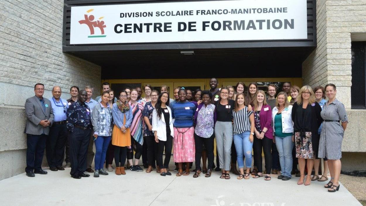 Devant le bâtiment de la DSFM, des adultes en groupe sourient à l'objectif.