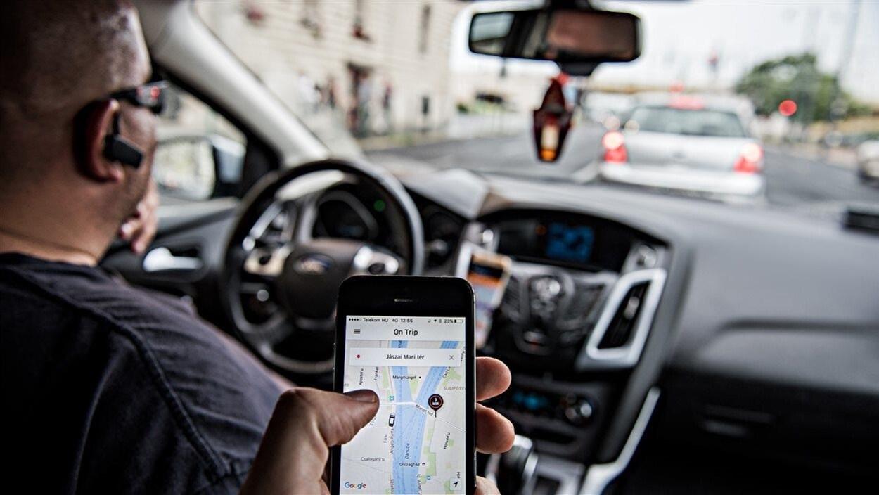 Dans une voiture un homme est volant pendant qu'une autre personne présente montre l'application Uber à partir d'un télephone