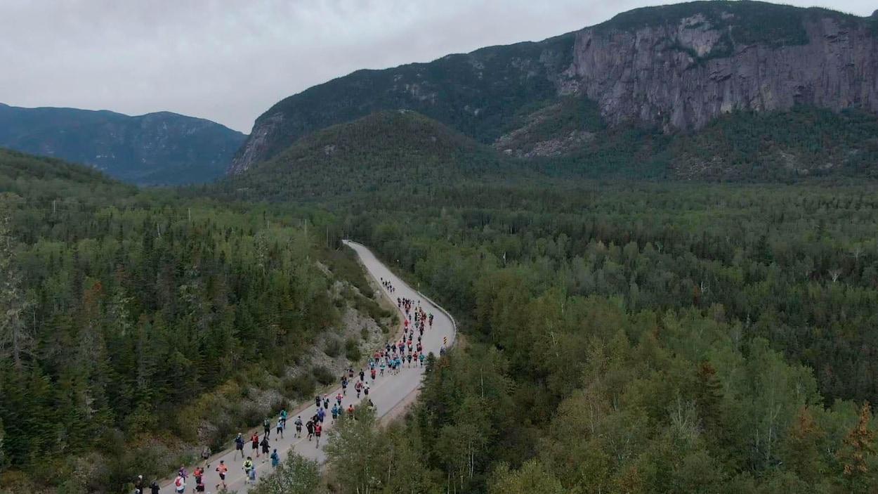 Des dizaines de personnes courent sur un sentier au milieu des bois.