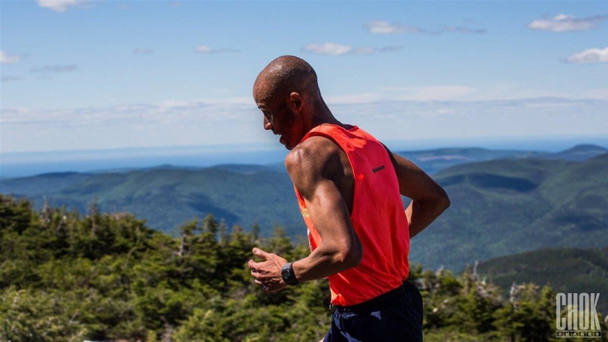 Un homme court au sommet d'une montagne qui domine le reste du paysage.