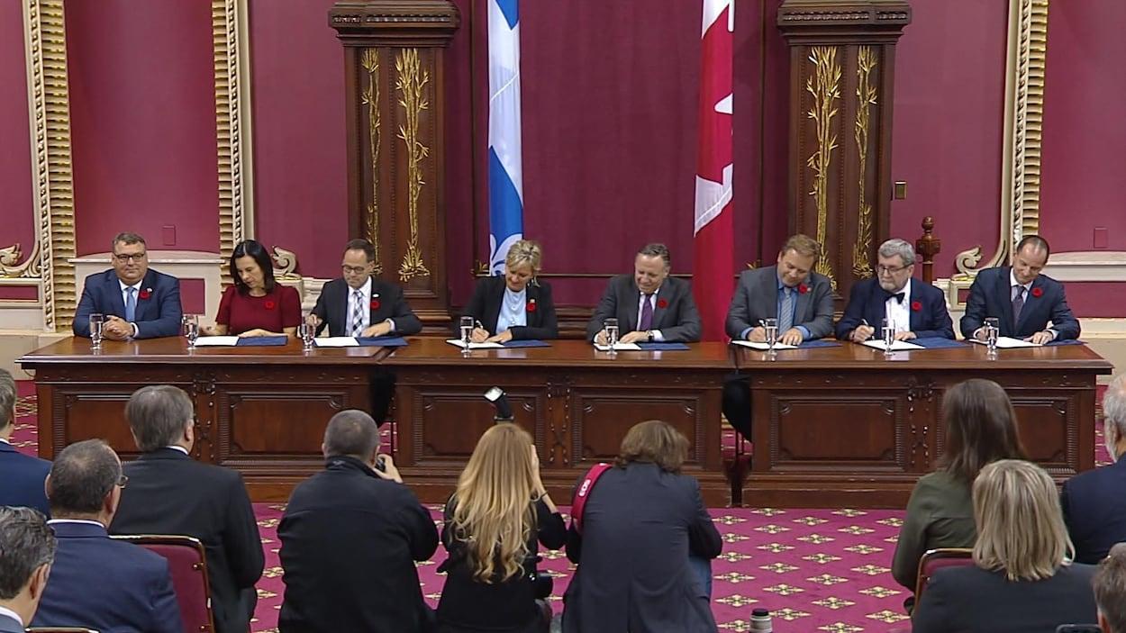 Les représentants de l'Union des municipalités du Québec et le gouvernement Legault signent le pacte fiscal.