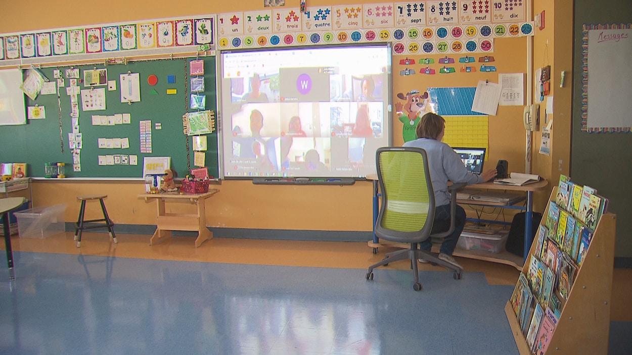 Une enseignante assise devant un ordinateur dans sa classe; au mur, un écran sur lequel est projetée une vidéoconférence, avec sa mosaïque de participants.