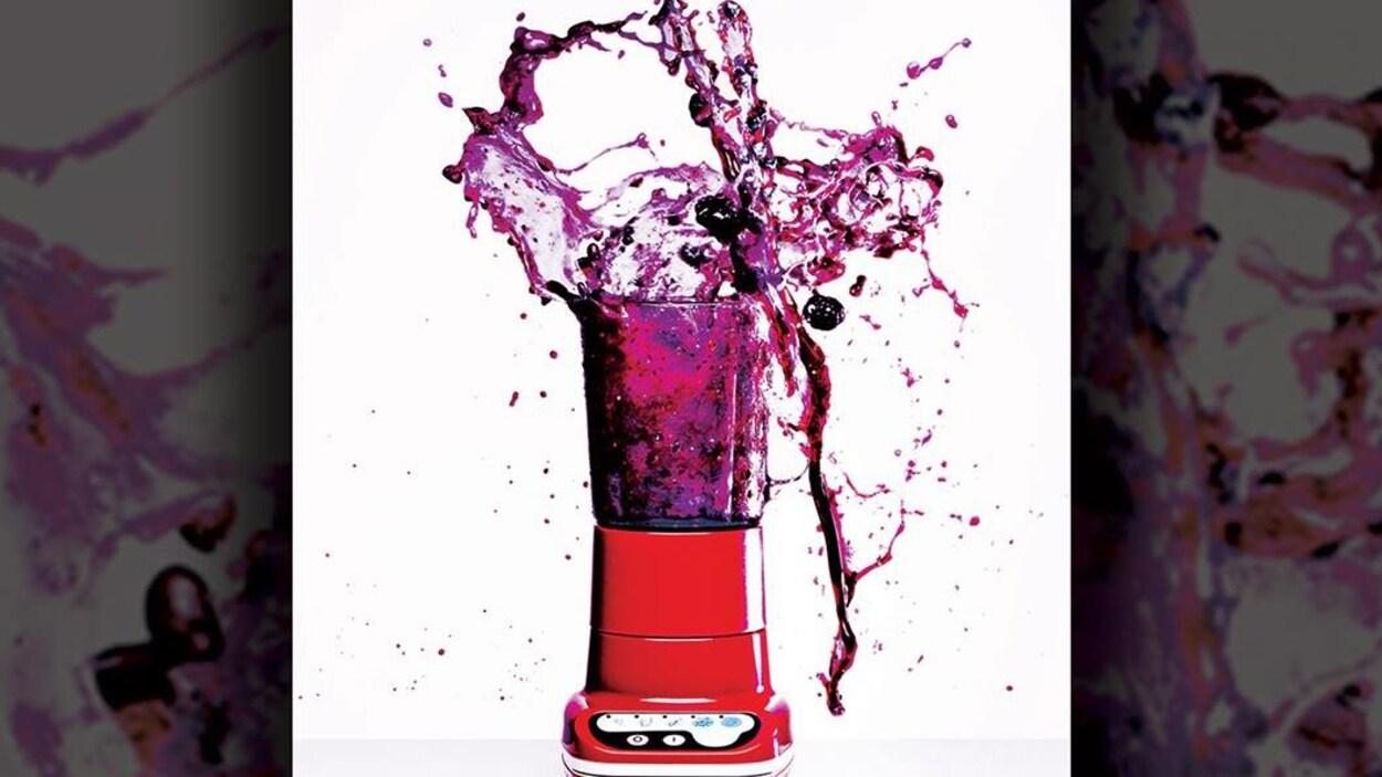 Photo d'un mélangeur rouge, couvercle ouvert, d'où s'échappe un liquide violet en giclant.