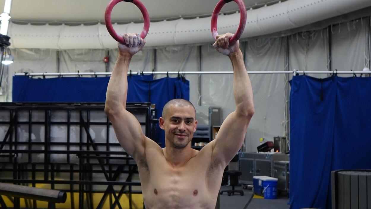La photo montre un homme qui sourit, les mains relevées et tenant des anneaux de cirque.
