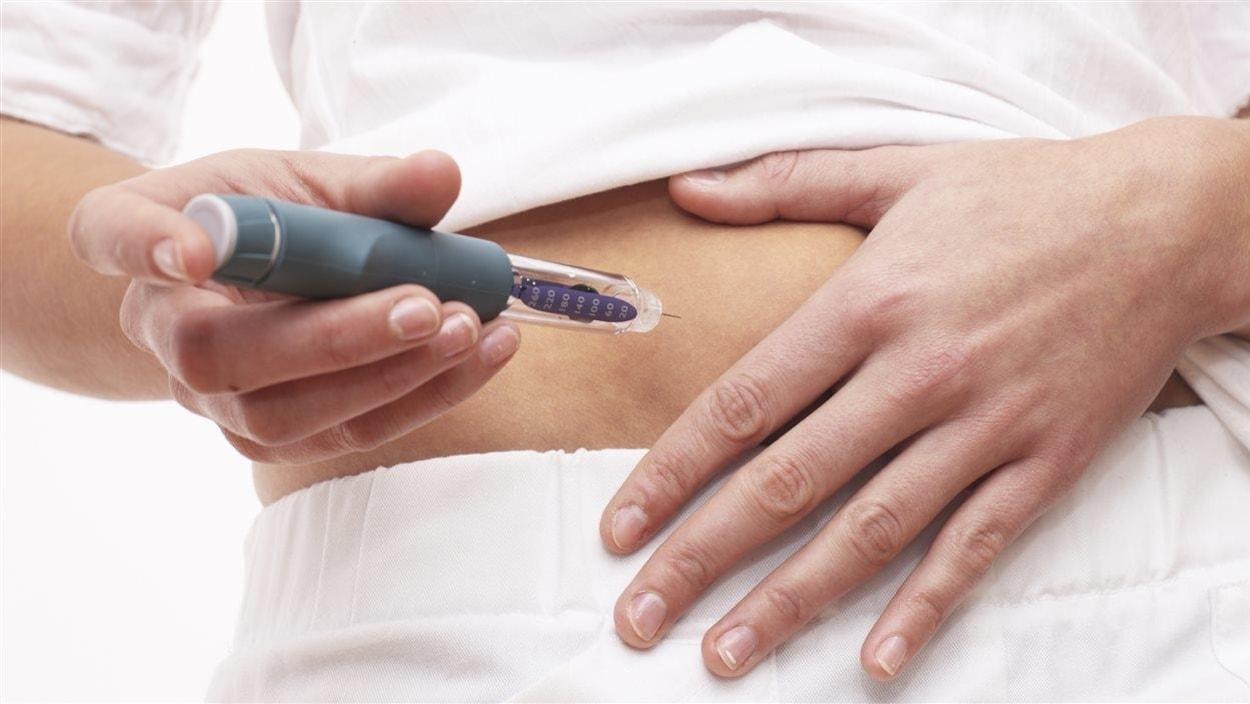 Une femme s'apprête à s'injecter une dose d'insuline dans l'abdomen.