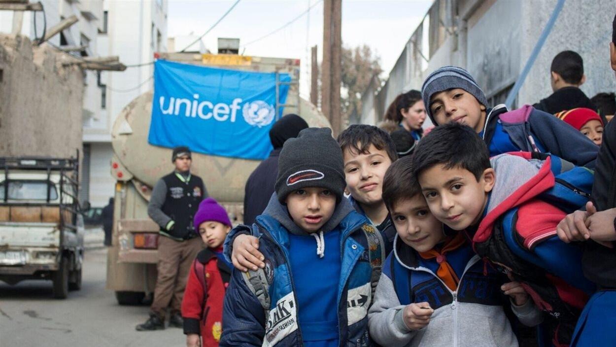 Des enfants posent devant un camion-citerne d'eau potable.
