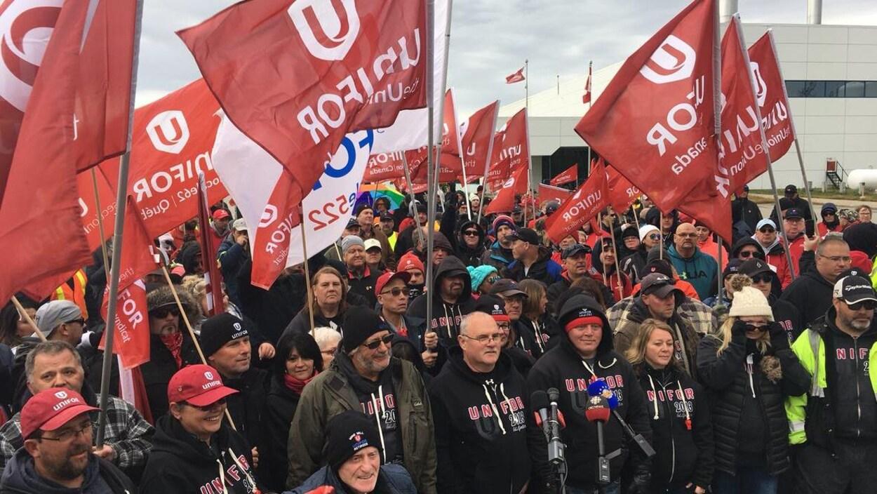Des manifestants agitant des drapeaux rouges d'Unifor.
