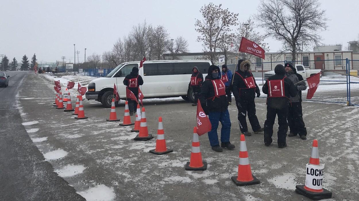 Deux petits groupes de personnes manifestent devant la raffinerie Co-op de Regina.