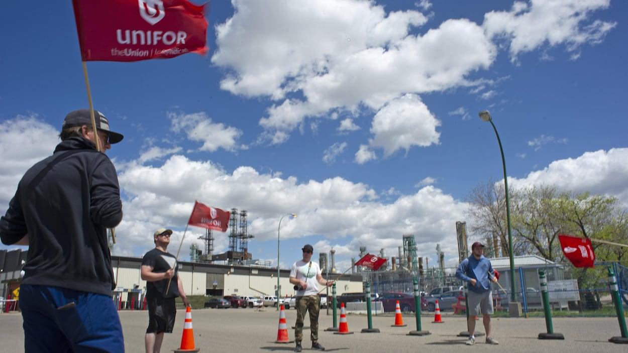 Des membres d'Unifor avec des drapeaux sont dehors tout près du site de la raffinerie Co-op de Regina.