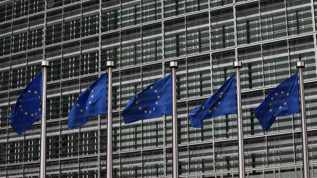Des drapeaux de l'Union européenne flottent devant un édifice à Bruxelles.