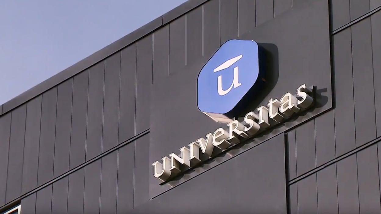 Gros plan sur le logo bleu d'Universitas sur le mur du bâtiment abritant leurs bureaux, à Québec.