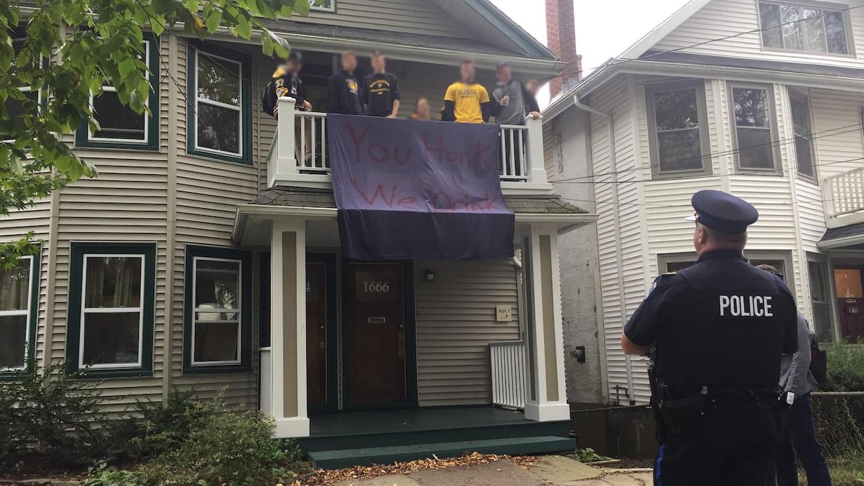 Des policiers sur le trottoir discutent avec des jeunes qui se trouvent sur un balcon à l'étage d'une maison.