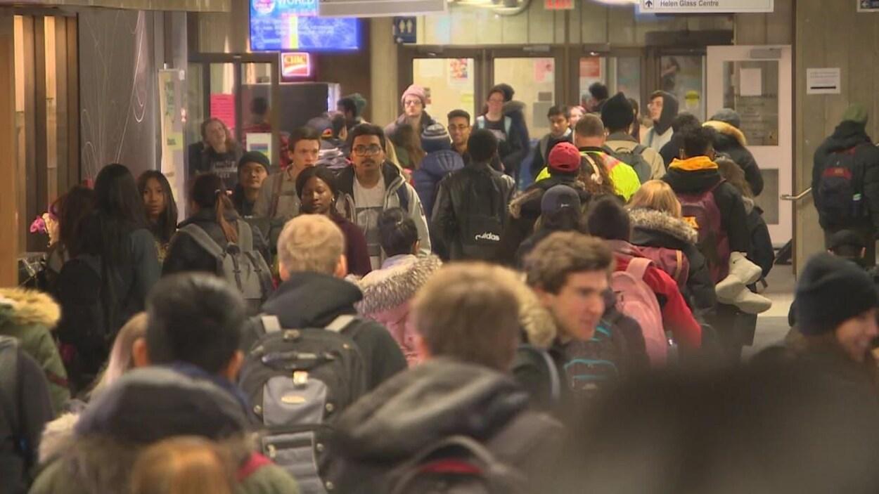 Des étudiants discutent et d'autres se déplacent dans un corridor de l'Université du Manitoba.